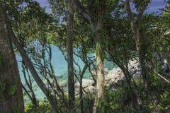 Overzeese mening door regenwoud om grote stenen en azuurblauw duidelijk water Mooie paradijslagune royalty-vrije stock afbeeldingen