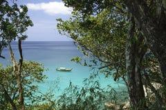 Overzeese mening en traditionele Thaise boot door regenwoud om grote stenen en azuurblauw duidelijk water stock foto's