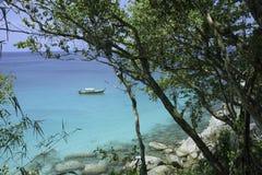 Overzeese mening en traditionele Thaise boot door regenwoud om grote stenen en azuurblauw duidelijk water royalty-vrije stock afbeelding