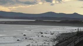 Overzeese Mening met bergen in de avond lichte, Welse kust stock footage