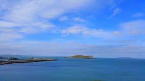 Overzeese mening met eiland en haven op de achtergrond Stock Afbeeldingen