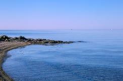 Overzeese mening van strand met zonnige hemel Stock Afbeelding