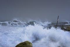 Overzeese onweersgolven die dramatisch en tegen rotsen verpletteren bespatten Royalty-vrije Stock Fotografie