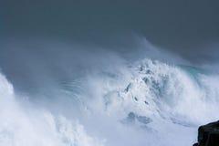 Overzeese onweersgolven die dramatisch en tegen rotsen verpletteren bespatten Stock Foto