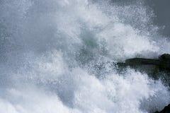 Overzeese onweersgolven die dramatisch en tegen rotsen verpletteren bespatten Stock Fotografie