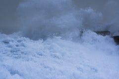 Overzeese onweersgolven die dramatisch en tegen rotsen verpletteren bespatten Royalty-vrije Stock Foto's
