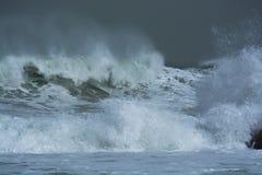 Overzeese onweersgolven die dramatisch en tegen rotsen verpletteren bespatten Royalty-vrije Stock Foto