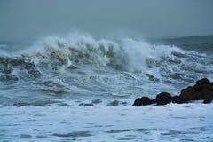 Overzeese onweersgolven die dramatisch en tegen rotsen verpletteren bespatten Royalty-vrije Stock Afbeelding