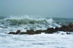 Overzeese onweersgolven die dramatisch en tegen rotsen verpletteren bespatten Stock Foto's
