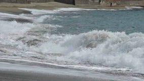 Overzeese rollende golven op kust die hen raken tegen grond en in schuim breken stock video