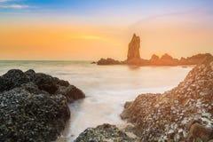 Overzeese rots met de achtergrond van de zonsonderganghorizon Stock Foto