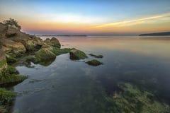 Overzeese rotsachtige kust met groen mos stock foto