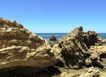 Overzeese rotsen en Strandmening stock afbeeldingen