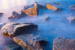 Overzeese rotsen in nevel bij zonsondergang stock afbeelding
