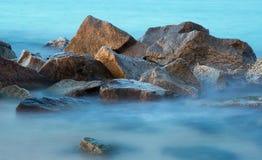 Overzeese rotsen in nevel bij zonsondergang stock fotografie