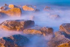 Overzeese rotsen in nevel bij zonsondergang royalty-vrije stock foto's