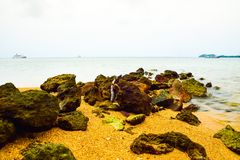 Overzeese rotsen op het gele zandige strand stock foto