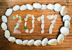 Overzeese shells en glasinschrijving 2017 op houten achtergrond Stock Fotografie