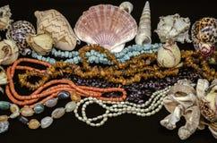 Overzeese shells en parels van turkoois, rood koraal, amber, granaatappel, kleurrijk agaat, parels onder op zwarte achtergrond stock afbeelding