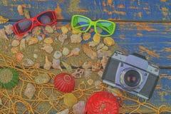 Overzeese Shells op een Blauwe Achtergrond De zomer reizende tijd Overzeese vakantieachtergrond met diverse shells, zonnebril en  Royalty-vrije Stock Foto's