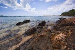 Overzeese strand en rots op blauwe hemel Royalty-vrije Stock Afbeelding