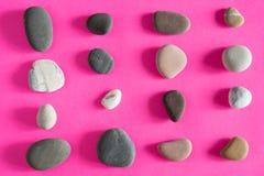 Overzeese van graniet vlotte kiezelstenen stenen op roze hoogste mening als achtergrond stock foto's