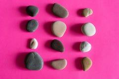 Overzeese van graniet vlotte kiezelstenen stenen op roze hoogste mening als achtergrond royalty-vrije stock foto