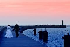 Overzeese van jonggehuwden zonsonderganggang Stock Foto