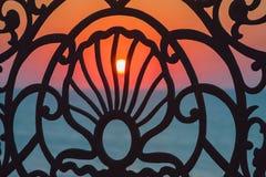 Overzeese Zonsondergang door de waterkant van het smeedijzertraliewerk Stock Afbeeldingen