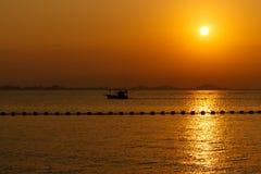 Overzeese zonsondergang met bootsilhouet Stock Afbeeldingen