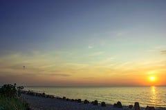 Overzeese zonsondergang met een silhouet van glijscherm Stock Foto