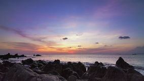 Overzeese zonsondergang op pan de tijdtijdspanne van de rotskust stock videobeelden