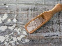 Overzeese zoute vlokken en houten lepel over schors op houten achtergrond Royalty-vrije Stock Fotografie