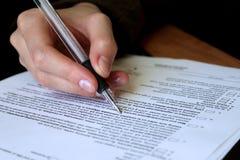 Overzicht en het invullen van wettelijk contract Stock Foto