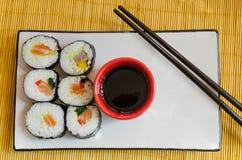Overzicht van zes sushibroodjes met sojasaus en eetstokjes Royalty-vrije Stock Afbeelding
