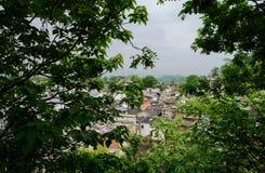 Overzie aan oude stad van bosrijke helling in de bewolkte lente royalty-vrije stock foto