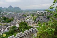 Overzie van steenmuur aan oude stad in bergen op bewolkt stock foto's