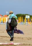Ovettig gatuförsäljare med tyger och klänningar som går på stranden Arkivbild