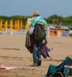 Ovettig gatuförsäljare med tyger och klänningar som går på strandglen Royaltyfri Bild