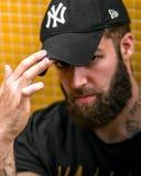 Oviedo, as Astúrias ESPANHA - 5 DE JULHO DE 2018 O retrato de um moderno novo tattooed o homem com chapéu dos New York Yankees imagens de stock royalty free