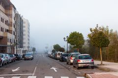 Cars parked along the road in Oviedo in the early morning with a thick morning fog Stock Photos
