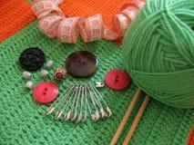 Ovillo, botones y aguja verdes para hacer punto Imagen de archivo libre de regalías