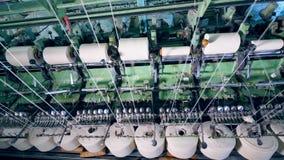 Ovillos blancos que hacen girar en las máquinas modernas en una fábrica de la materia textil metrajes
