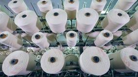 Ovillos grandes con la fibra que gira en un estante en una fábrica de la materia textil almacen de video