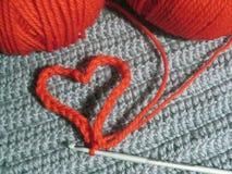Ovillos rojos de las lanas y corazón hecho punto Imagen de archivo