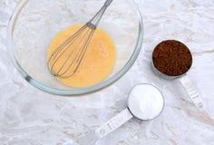 Ovo batido com os copos do batedor de ovos e de medição do açúcar Imagens de Stock Royalty Free