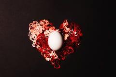 Ovo branco no coração vermelho fotografia de stock