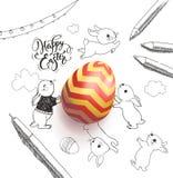 Ovo colorido brilhante cercado pelo desejo feliz do feriado da Páscoa escrito à mão com fonte caligráfica, coelhos pequenos engra Imagens de Stock