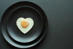 Ovo coração-dado forma delicioso do frango frito em placas cerâmicas pretas no estilo mínimo do fundo preto Cozimento do â imagem de stock royalty free