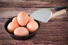 Ovo da galinha de Brown e bandeja do ferro na tabela Foto de Stock